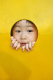 Asian girl sticks face through hole in playground. A little girl sticks her face through a hole in a yellow plastic piece of playground equipment royalty free stock photos