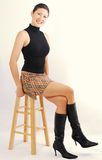 Asian Girl on a Stool. Pretty Asian Girl posed perkily on a wooden srool Royalty Free Stock Photo
