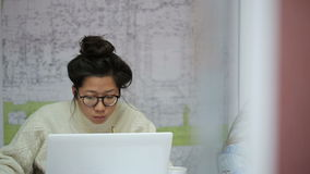 Asian girl student with glasses reading a synopsis on laying urban communications. She wore a white woolen sweater or pullover that is greater than its size stock footage