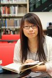 Asian girl student reading and studying in library Stock Image