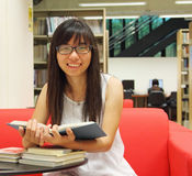 Asian girl student reading and studying in library Royalty Free Stock Images