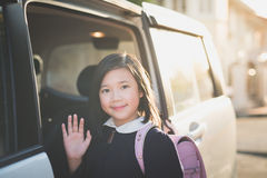 Asian girl in student uniform going to school by car. And  waving goodbye Royalty Free Stock Images
