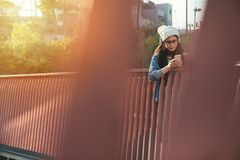Asian girl student using the smartphone. Candid shot of beautiful Asian girl student using the smartphone on the river bridge Royalty Free Stock Image