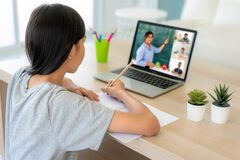 Asian girl student video conference e-learning with teacher and classmates on computer in living room at home. Homeschooling and