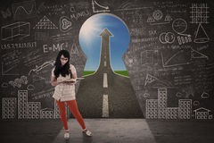 Asian girl study in front of keyhole success road. Asian girl is studying in front of keyhole success road landscape royalty free stock photography