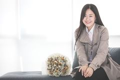 Asian girl in a suit sitting on sofa at the window. smile happil stock image