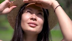 Asian girl in a summer hat looking into the sky. Something is looking out. The eyes are shield from the sun by the hand.