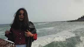Asian girl in sunglasses by the sea. Wind develops hair.  stock video