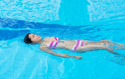 An Asian girl is swimming backstroke in the swimmi. An Asian girl is swimming backstroke in the blue clean water of the swimming pool Stock Photography