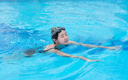 An Asian girl is swimming in the swimming pool Royalty Free Stock Photography