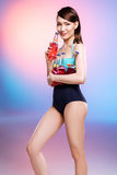 Asian girl in swimsuit holding glass bottles with lollipops and looking at camera. Smiling asian girl in swimsuit holding glass bottles with lollipops and Stock Photo