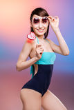 Asian girl in swimsuit holding lollipop and adjusting sunglasses Stock Photo