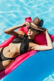 asian girl in swimsuit and straw hat relaxing on inflatable mattress stock images