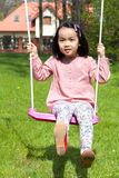 Asian girl swinging in a garden Stock Images