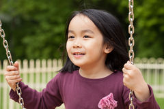 Asian girl swinging on a swing Stock Photos