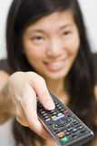 Asian girl switching channels Royalty Free Stock Photos