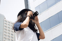 Asian girl take photo in city. Asian girl take photo with camera in modern urban city outdoor Stock Image