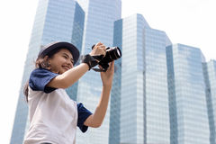 Asian girl take photo in city. Asian girl take photo with camera in modern urban city outdoor Stock Images