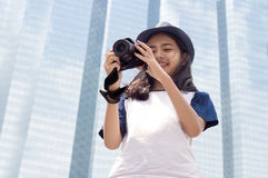 Asian girl take photo in city. Asian girl take photo with camera in modern urban city outdoor Royalty Free Stock Images