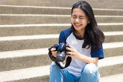 Asian girl take photo in city. Select focus happy face of asian teenage like to take photo with camera to be stocker gig economy Stock Photography