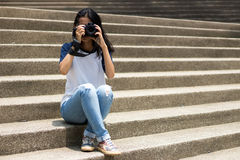 Asian girl take photo in city. Asian teenage like to take photo with camera to be stocker gig economy Stock Photo