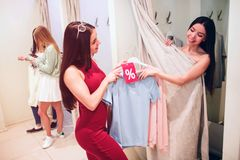 Asian girl is taking blue and pink discount shirts from girl in red dress. She wants to try them on herself. There are royalty free stock photography