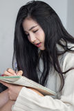 Asian girl taking notes. Asian girl taking a notes Stock Image