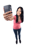 Asian girl taking a photo of herself. A wide angle full body shot of an Asian girl holding a camera far in front of herself getting ready to take a photo of Royalty Free Stock Photo
