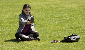 Asian girl taking selfie photo. Berlin, Germany - Mai 30, 2014:Asian girl taking selfie photo.She sitting on the lawn around the Island Museum in Berlin Royalty Free Stock Photo