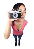 Asian girl taking a snapshot. A wide angle full body shot of an Asian girl holding a camera in front of her face getting ready to take a photo Stock Photography