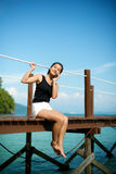 Asian girl talking on the phone at a pier Royalty Free Stock Image
