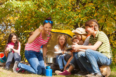 Asian girl tastes soup in metallic pot at campsite Stock Images