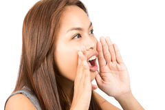 Asian Girl Telling Secret Hands Protecting Mouth. Close up of young, adorable Asian girl with light brown hair telling secret gossip protecting her mouth with stock image