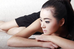 Asian girl thinking on sofa. Asian girl in dark dress lying on the sofa.she is thinking Stock Photos
