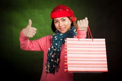Asian girl  thumbs up with christmas hat and shopping bag Stock Image