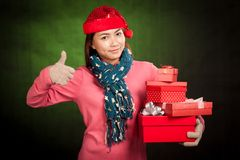 Asian girl  thumbs up with red christmas hat and gift boxes Stock Images