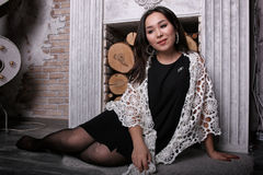 Asian girl in torn pantyhose sitting near the fireplace with the shawl on his shoulders royalty free stock photo