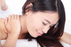 Asian girl touching shoulders on bed Stock Photography