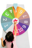 Asian girl trying to spin the huge colorful fortune wheel with w. Hite digit numbers isolated on white background Royalty Free Stock Images