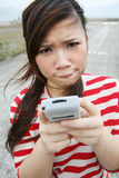 Asian girl using her PDA Royalty Free Stock Images