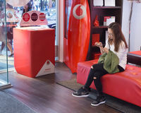 Asian girl using a mobile. Auckland, New Zealand - February 17, 2017: Asian girl using her mobile inside a vodafone store in Auckland Stock Photos