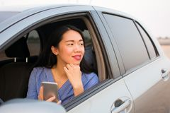 Asian girl using phone in car Royalty Free Stock Photo
