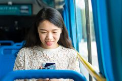 Girl using phone on public bus Stock Photos