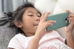 Asian girl using smartphone and laying on sofa Royalty Free Stock Photo
