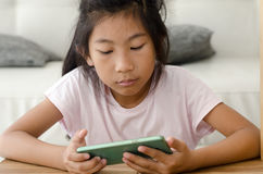 Asian girl using smartphone in living room Stock Image