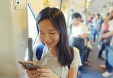 Asian girl using a smartphone in mass rapid transit among people Stock Images