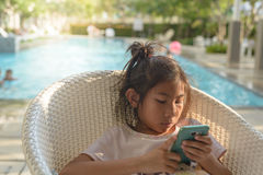 Asian girl using smartphone with swiming pool Royalty Free Stock Photography