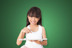 Asian girl using tablet PC. Over green background with clipping path Royalty Free Stock Images