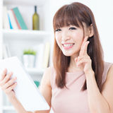 Asian girl using tablet showing peace hand sign Stock Photo