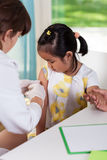 Asian girl during vaccine. At doctor's office royalty free stock image